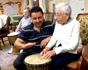 A man teaching seniors to play bongos