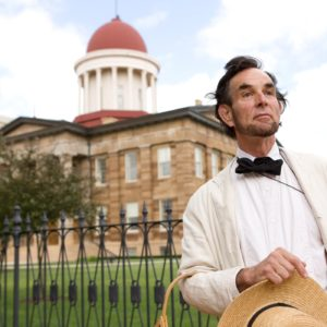 An Abe Lincoln lookalike poses in front of Springfield's historic state capitol building