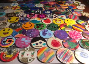A selection of the more than 5,500 painted wooden disks submitted to JCPRC before being attached to the permanent art installation in Shenandoah Junction's AMP field.