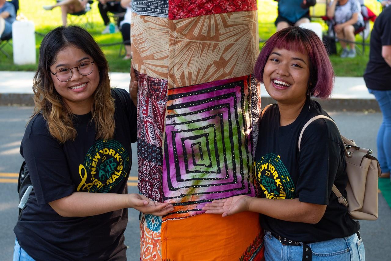 Levitt AMP Utica youth participants Eh Pleh Hsoe (right) and Doe Kpaw So Paw's (left) fabric wrap fabrics around trees at Kopernik Park in 2019 (Levitt AMP Utica)